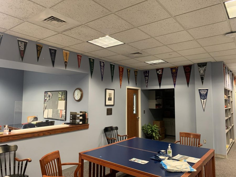 A variety of college pennants line the wall of the College Counseling Office. Photo by Anthony Wise
